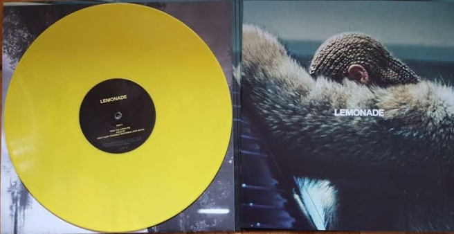 Till höger en gul vinylskiva. Till vänster omslagsfotot till Beyoncés skiva Lemonade