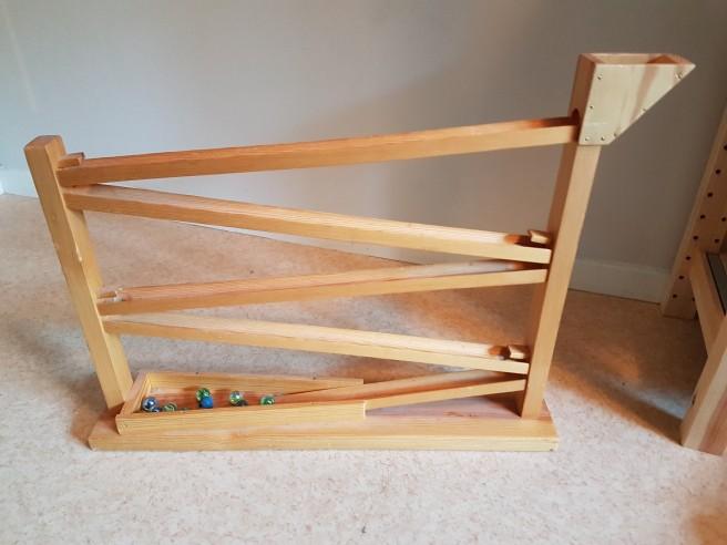 En kulbana i trä. Man lägger i kulorna längst upp och så åker kulorna i banor fram och tillbaka tills den stannar längst ner.