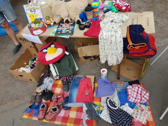 Ett bord på en loppmarknad med lite leksaker, barnböcker och barnkläder. Framför på marken ligger också barnkläder och barnskor på en filt.