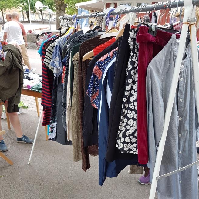 En klädhängare med kläder som en person säljer på loppmarknaden.